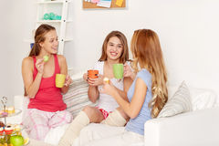 Jeunes femmes heureuses buvant du thé avec des bonbons à la maison Photo stock