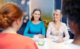 Jeunes femmes heureuses buvant du thé ou du café au café Photo stock