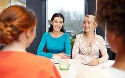 Jeunes femmes heureuses buvant du thé ou du café au café Image stock