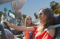 Jeunes femmes heureuses conduisant dans la voiture au-dessus de la plage de Venise Photos libres de droits