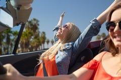 Jeunes femmes heureuses conduisant dans la voiture au-dessus de la plage de Venise Photographie stock libre de droits