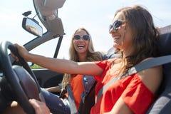Jeunes femmes heureuses conduisant dans la voiture de cabriolet Photographie stock libre de droits