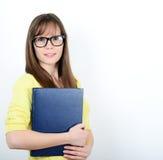 Jeunes femmes heureuses d'étudiant tenant des livres dans sa main tandis que standi Photographie stock libre de droits