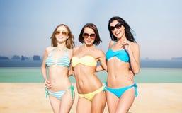 Jeunes femmes heureuses dans des bikinis sur la plage d'été Photos stock