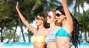 Jeunes femmes heureuses dans des bikinis sur la plage d'été Photo stock