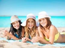 Jeunes femmes heureuses dans des bikinis sur la plage d'été Image stock
