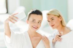 jeunes femmes heureuses dans des peignoirs prenant le selfie Image libre de droits