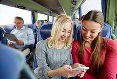 Jeunes femmes heureuses dans l'autobus de voyage avec le smartphone Photographie stock libre de droits