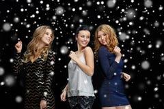 Jeunes femmes heureuses dansant à la disco de boîte de nuit Photos stock