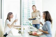 Jeunes femmes heureuses dinning ensemble Photographie stock libre de droits