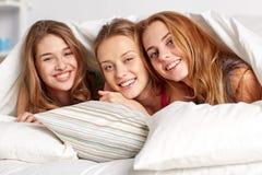 Jeunes femmes heureuses en partie de pyjama de lit à la maison Image stock