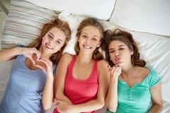 Jeunes femmes heureuses en partie de pyjama de lit à la maison Photos stock