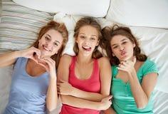 Jeunes femmes heureuses en partie de pyjama de lit à la maison Photos libres de droits