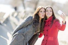 Jeunes femmes heureuses prenant la photo avec le téléphone portable Images libres de droits