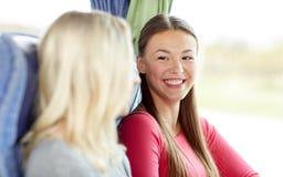 Jeunes femmes heureuses s'asseyant dans l'autobus de voyage Photographie stock libre de droits