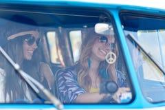 Jeunes femmes hippies de sourire conduisant la voiture de monospace Image libre de droits