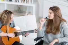 Jeunes femmes jouant la guitare tandis que chant d'ami de fauteuil roulant Photographie stock libre de droits
