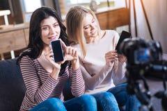 Jeunes femmes joyeuses montrant leurs smartphones Photos stock