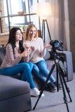 Jeunes femmes joyeuses s'asseyant ensemble sur le sofa Photo libre de droits