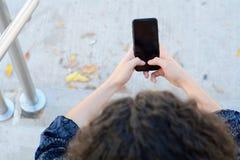 Jeunes femmes latines envoyant le message avec le smartphone photographie stock