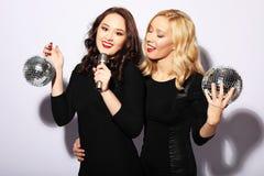 Jeunes femmes magnifiques dans des robes de fête chantant le karaoke Photographie stock libre de droits