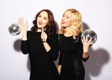 Jeunes femmes magnifiques dans des robes de fête chantant le karaoke Photographie stock