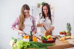 Jeunes femmes magnifiques préparant le dîner dans une cuisine Photographie stock