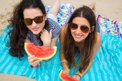 Jeunes femmes mangeant la pastèque sur la plage Photographie stock libre de droits