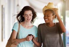 Jeunes femmes marchant ensemble utilisant le téléphone portable Image libre de droits