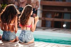 Jeunes femmes mignonnes s'asseyant près de la piscine et du jus potable Photo libre de droits