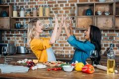 Jeunes femmes miltiehnic donnant la haute cinq tout en faisant cuire dans la cuisine Image stock