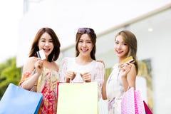 jeunes femmes montrant les paniers et la carte de crédit Photographie stock libre de droits