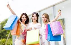 jeunes femmes montrant les paniers et la carte de crédit Images stock