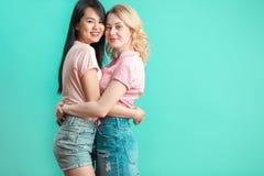 Jeunes femmes multi-ethniques étreignant au fond bleu de studio avec l'espace de copie Images libres de droits