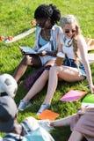 Jeunes femmes multi-ethniques étudiant tout en se reposant sur l'herbe en parc Images stock
