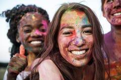 Jeunes femmes multi-ethniques avec la peinture colorée sur des vêtements et des corps ayant l'amusement ensemble au festival de h photo libre de droits