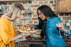 Jeunes femmes multi-ethniques de sourire mangeant de la pizza et buvant du vin à la cuisine Image libre de droits