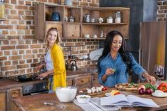 Jeunes femmes multi-ethniques faisant cuire ensemble dans la cuisine Images libres de droits