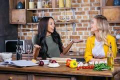 Jeunes femmes multi-ethniques faisant cuire ensemble et parlant dans la cuisine Image libre de droits