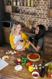 Jeunes femmes multi-ethniques faisant tinter des verres de vin tout en faisant cuire la pizza Image libre de droits