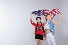 Jeunes femmes multi-ethniques heureuses tenant et tenant le drapeau des Etats-Unis Photos libres de droits