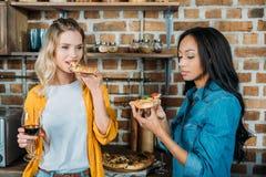 Jeunes femmes multi-ethniques mangeant de la pizza et buvant du vin à la maison Photo stock