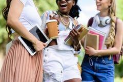 Jeunes femmes multi-ethniques tenant les livres et le comprimé numérique tout en parlant en parc Photographie stock libre de droits