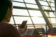 Jeunes femmes observant sur voler de attente de téléphone portable à la fenêtre d'aéroport Photo libre de droits