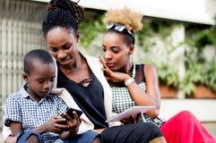 Jeunes femmes observant un petit garçon manipuler un téléphone portable Images stock