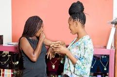 Jeunes femmes parlant la position devant le compteur d'un magasin de bijoux image stock
