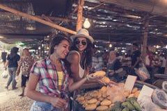 Jeunes femmes parlant tandis que fruits exotiques d'achat sur les touristes de sourire heureux de Girld du marché tropical dans l Photographie stock