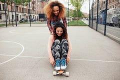 Jeunes femmes patinant à un terrain de basket Photos stock