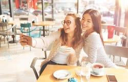 Jeunes femmes positives faisant des selfies ensemble Photographie stock