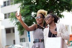 Jeunes femmes prenant des photos de selfie par leur téléphone intelligent Images stock